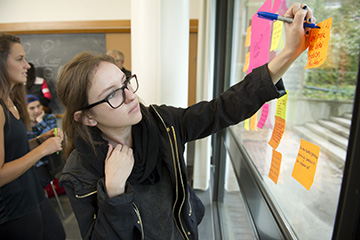 A photo shows a student is writing on a sticky note.